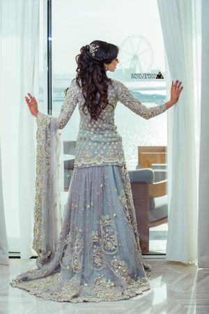 Photo of Bridal back shot in ice blue lehenga posing against window