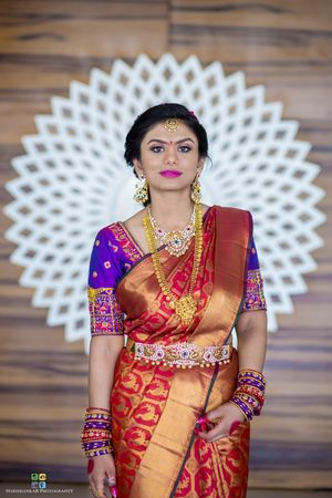 Bridal saree in red and gold with purple blouse