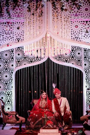 A couple pose during their wedding at a uniquely done mandap