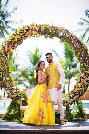 Mehendi couple portrait against giant wreath decor