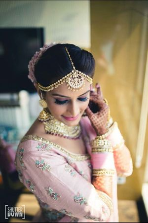 A bride in light pink lehenga and pink chooda