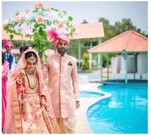 A bride enters under a floral umbrella