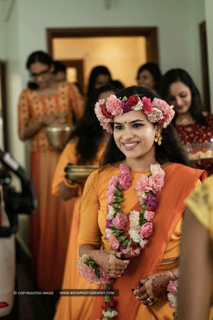 A bride in an orange outfit and floral jewelry for her haldi ceremony