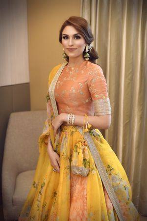 A bride poses in a coral and yellow light lehenga
