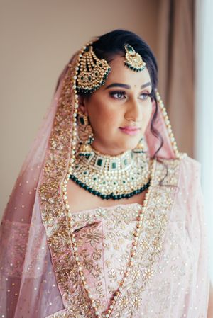 Contrasting jewellery with green beads with pastel lehenga