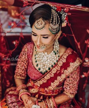 Bride in red lehenga and green jewellery with maangtikka and jhoomer