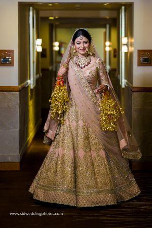 Bride twirls in pink and gold lehenga