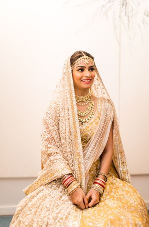 Bride in yellow lehenga, with double dupatta