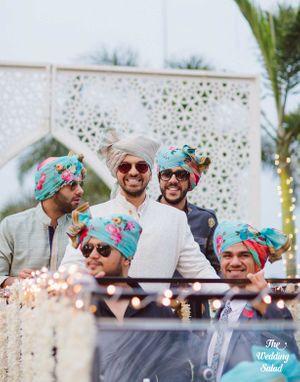 Groom entering with groomsmen wearing matching floral safas