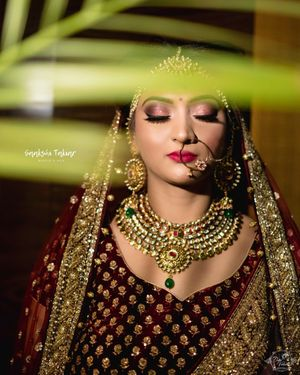 A bride in maroon lehenga and gold jewellery