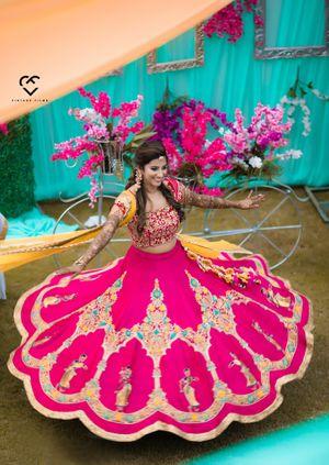 A bride in pink lehenga twirls on her mehendi day