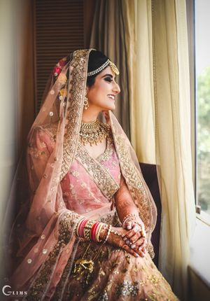 A bride in an onion pink and gold lehenga on her wedding day