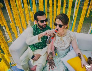 A groom to be helps his to be bride with a drink on her mehendi day