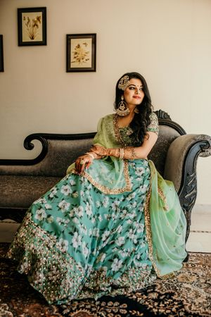 Mehendi bridal look in green lehenga and jhoomar