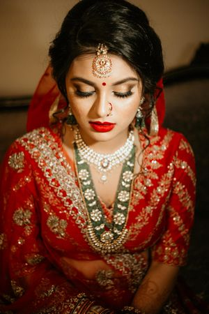 Bridal makeup with red lehenga and contrasting jewellery