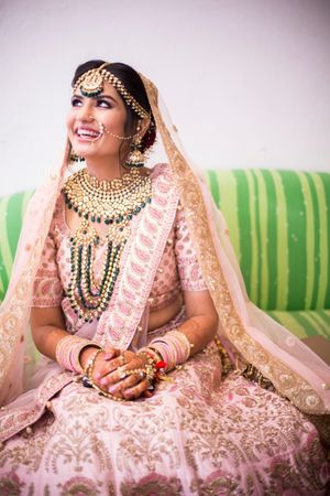 A bride in a soft pink lehenga and contrasting jewellery laughing for the camera