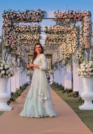 A bride posing in front of floral entrance decor