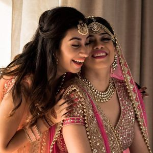 A bride all decked up for her big day laughing with her sister