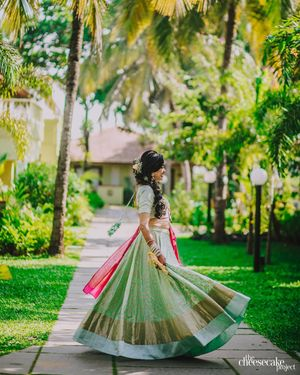 A bride twirling in her pastel green lehenga.