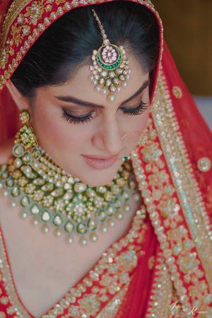 Bridal necklace and maangtikka contrasting to her lehenga