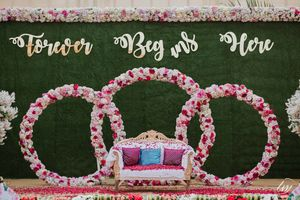 Engagement stage decor with botanical wall and floral installment