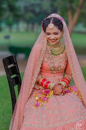 Happy bride shot in peach lehenga and red chura