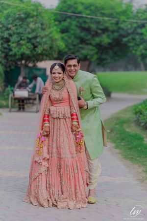 Contrasting bride and groom outfits in peach and light green
