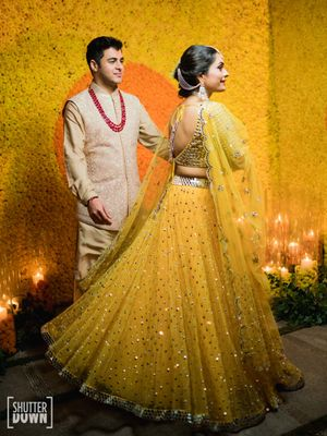 A couple coordinating in yellow and creme on their mehendi ceremony