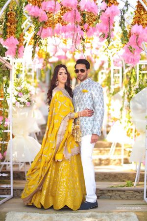 A bride in yellow lehenga poses with her husband-to-be on her mehendi day