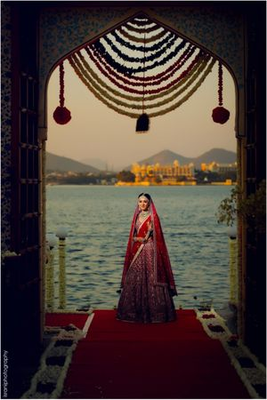 A bride in a red lehenga poses in front of a lake in Udaipur