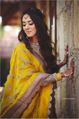 A bride in a yellow lehenga for her wedding