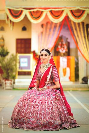 A bride in a red lehenga with double dupatta on her wedding day