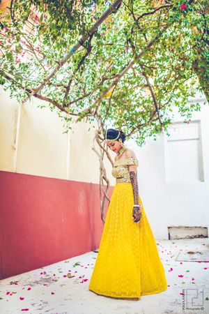 Gold off-shoulder blouse with mirror work and yellow skirt