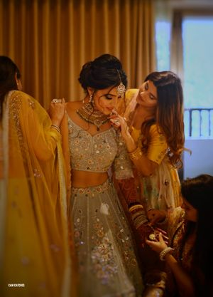 Bridesmaids helping bride in green lehenga get ready