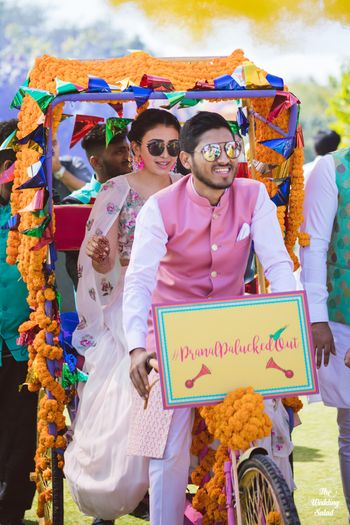 Photo of bride and groom entering together on mehendi in decorated rickshaw