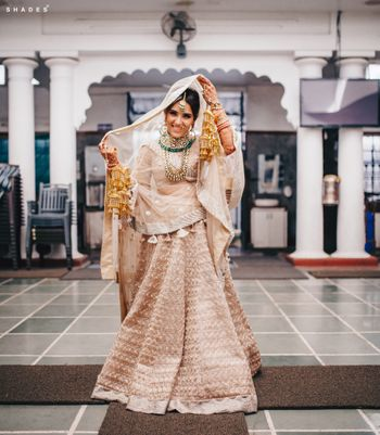 Photo of A Sikh bride posing in an off white and gold lehenga before her Anand Karaj ceremony