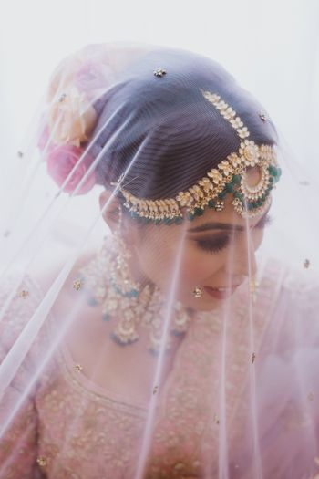 Photo of A glamorous bridal shot under dupatta as veil.