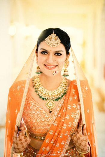 A bride in orange with gold and turquoise jewellery poses for the camera.