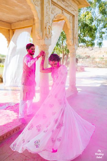 Photo of couple shot with twirling bride during holi mehendi
