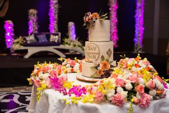 Photo of white wedding cake indian with pink flowers