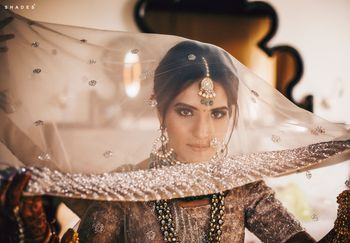 Photo of A bride getting ready, with a dupatta as a veil on her head