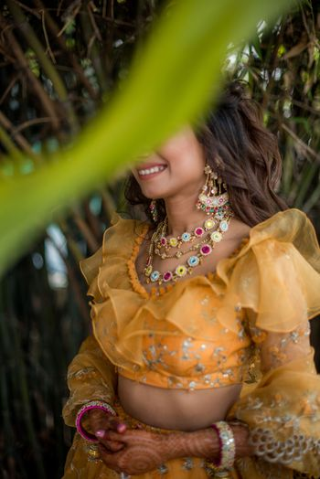 Funky mehendi jewellery with a yellow lehenga