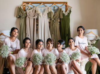 Photo of Bridesmaids with dresses on hanger