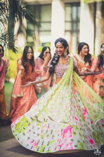 Photo of Bride twirling in unique mehendi lehenga with bridesmaids