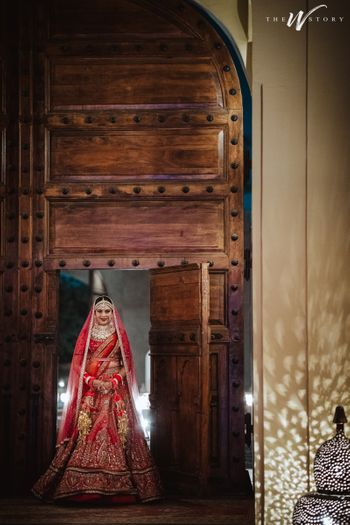Bride entering through a huge wooden gate.