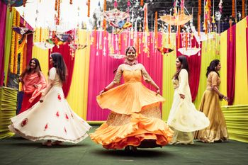 Photo of dancing bride with bridesmaids on her mehendi