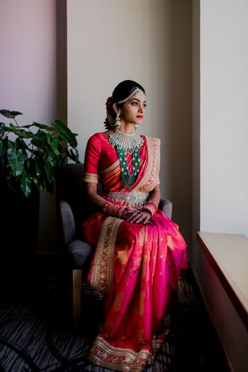 A south Indian bride in a red kanjeervaram and layered jewelry