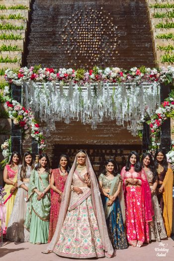 Photo of cute bride with bridesmaids shot idea against mandap