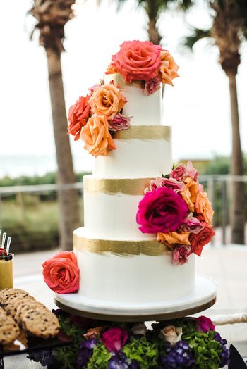 Photo of White and gold 4 tier wedding cake with flowers