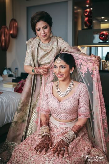 Photo of bride with mom placing her unique dupatta on head